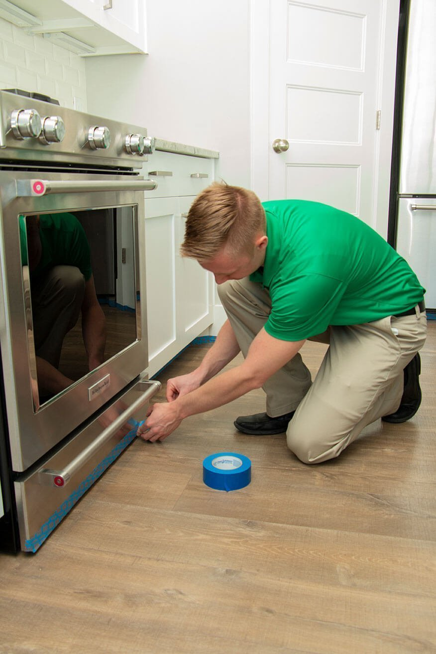 wood floor cleaning technician taping off appliances